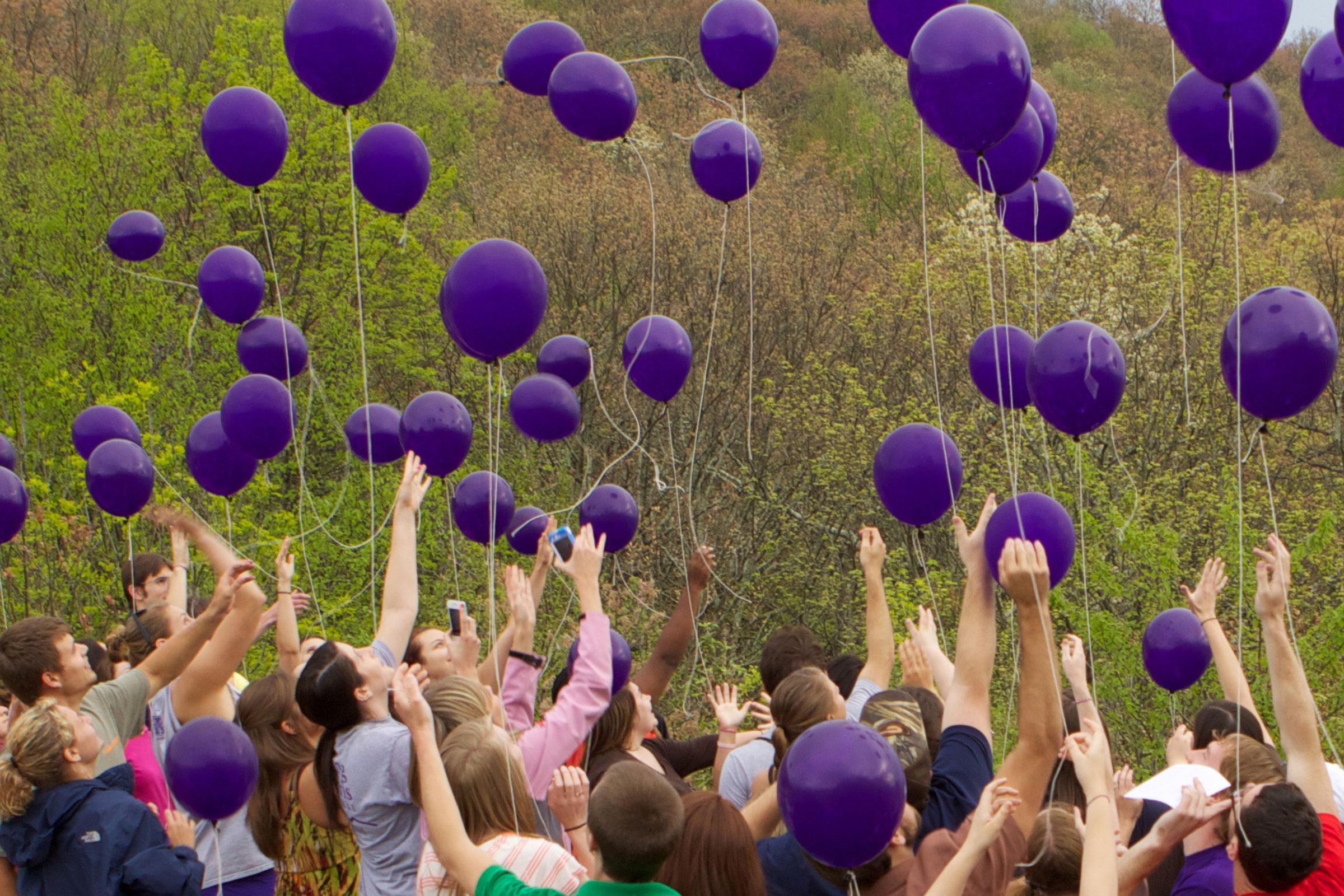 students releasing purple balloons in field