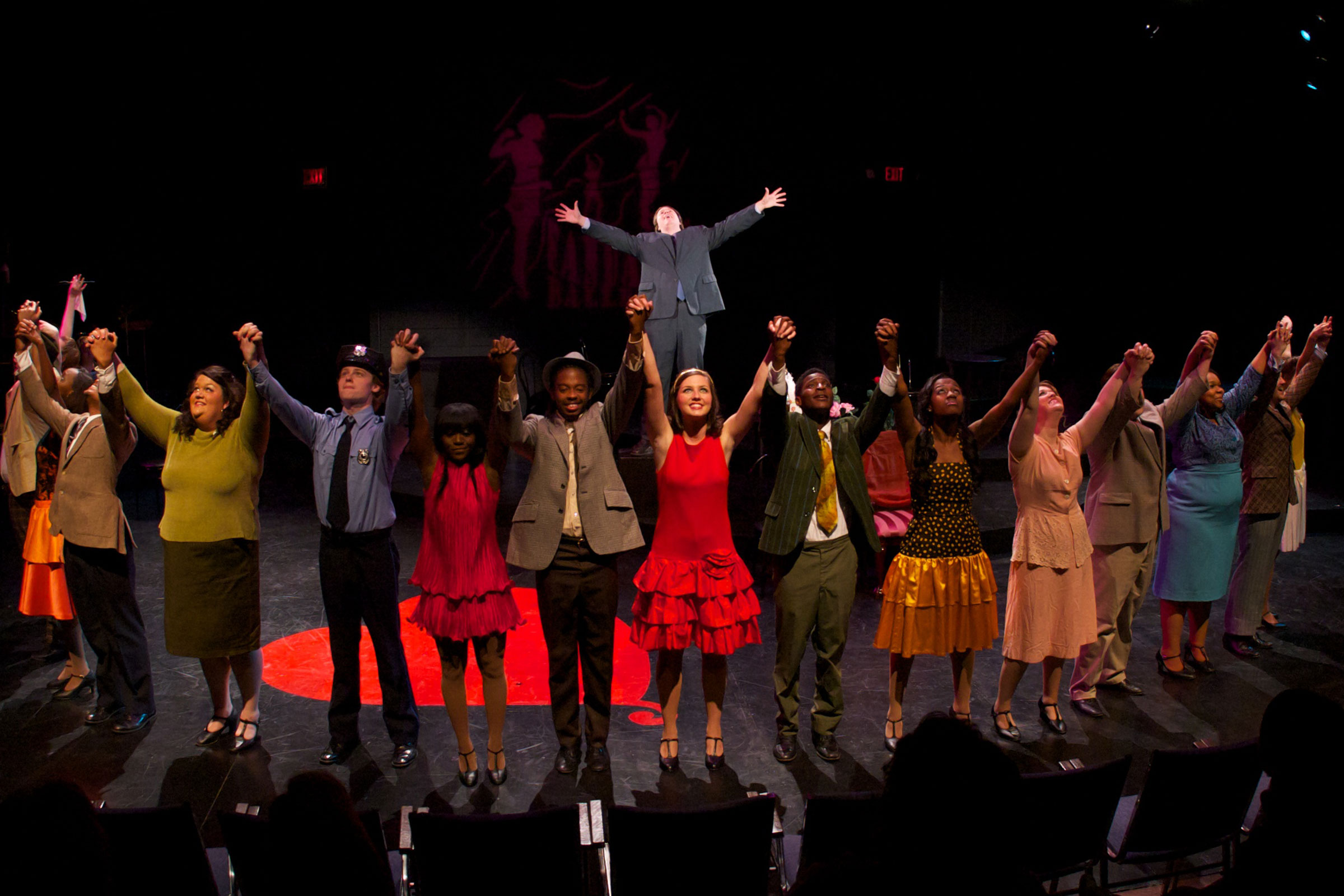 actors on stage arms raised