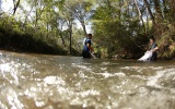 student wading in river