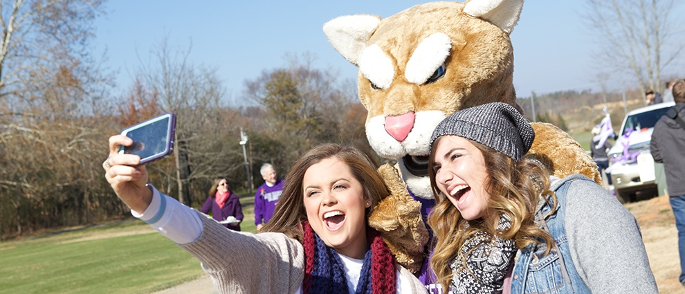 students taking selfie with mascot