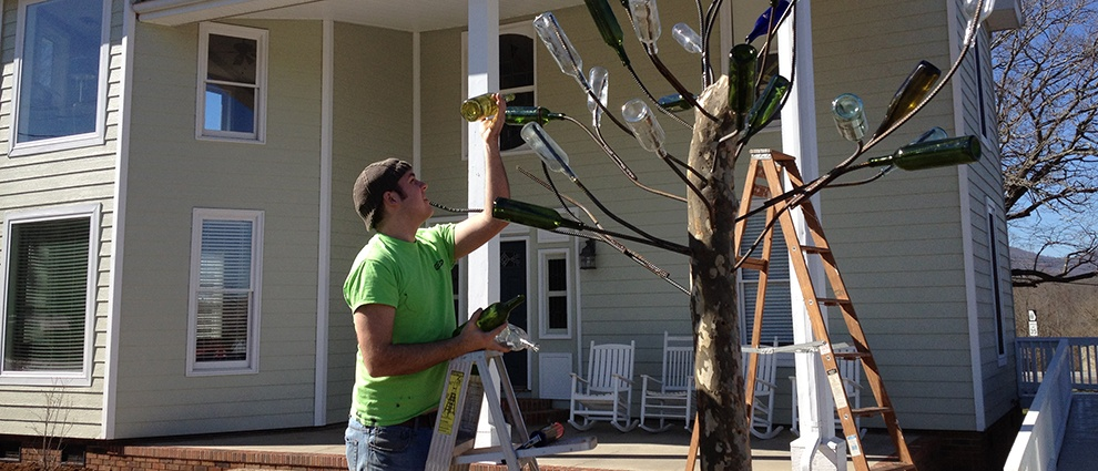 man installing bottles on trees