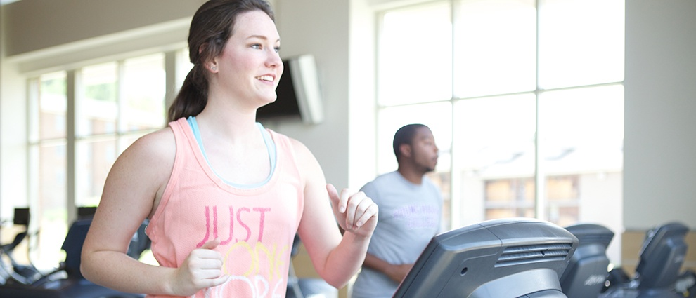 student using treadmill at recreation center