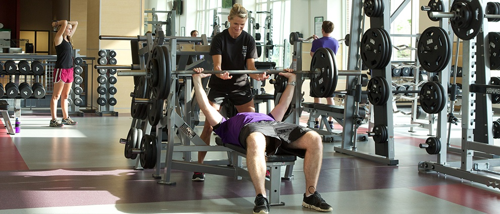 students lifting weights at recreation center