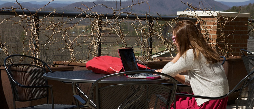 student on computer at outside table