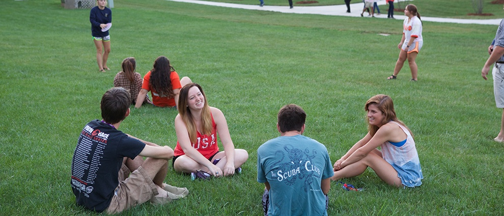 students sitting in circle on lawn