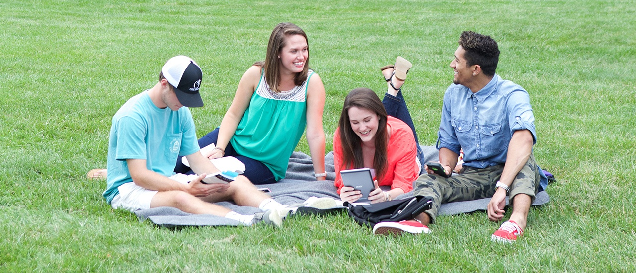 students on blanket on lawn