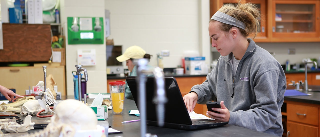 student on laptop in science class