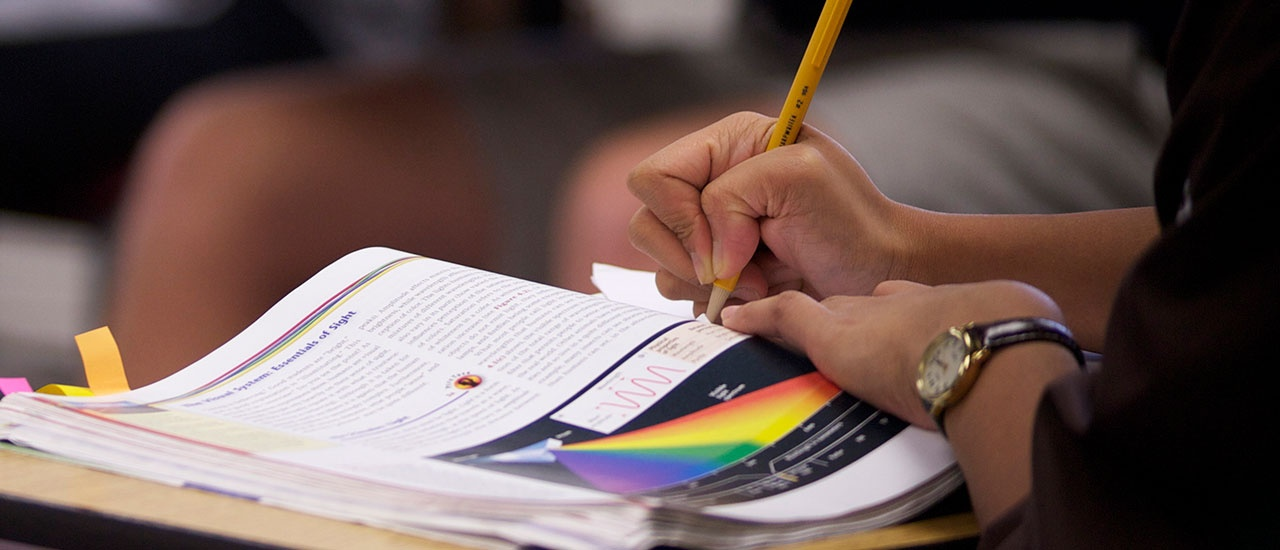 student taking notes from textbook