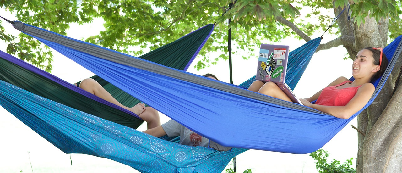student reading book in hammock