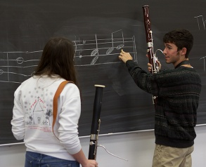 students writing music on chalk board