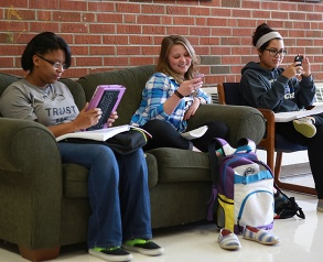 students on couch using phones