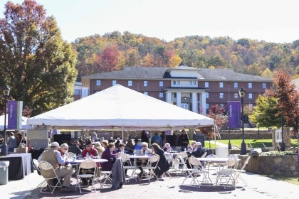 "YHC alumni enjoyed food and drinks on the campus plaza while watching football on TV and reconnecting with friends at ""A Weekend in the Enchanted Valley."""