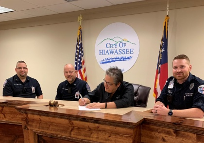 Young Harris College Police Department (YHCPD) Assistant Chief Robbie Rich, YHCPD Chief Ken Henderson, Hiawassee Mayor Liz Ordiales and Hiawassee Police Department Chief Paul Smith sign a memorandum of understanding for the two agencies to provide law enforcement support to one another when needed.